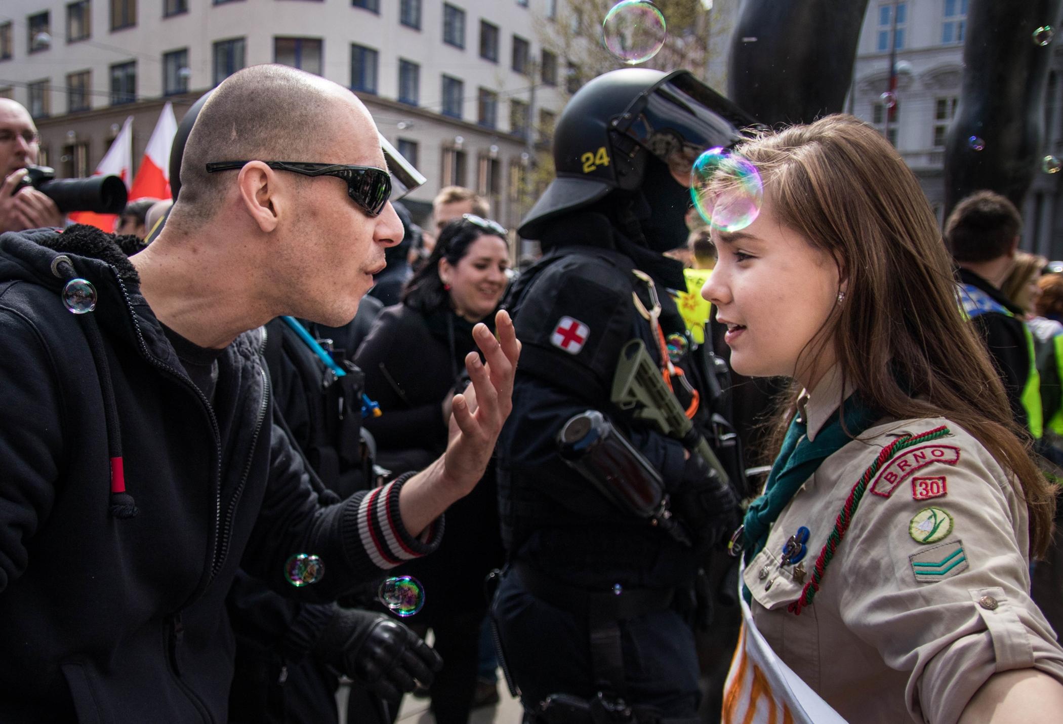 Skautka Lucie na virální fotce stojí tváří v tvář průvodu neonacistů během prvomájové akce Kdo si hraje, nehajluje