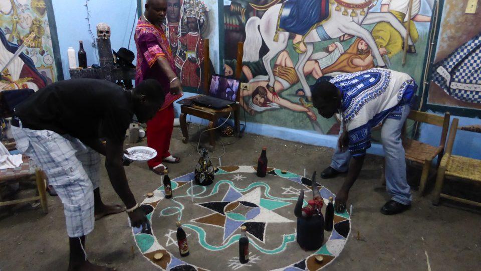 Vysypávání barevného vévé, které jsou v kurzu v hlavním městě Haiti. Hlavní kněz přikazuje, ostatní poslouchají