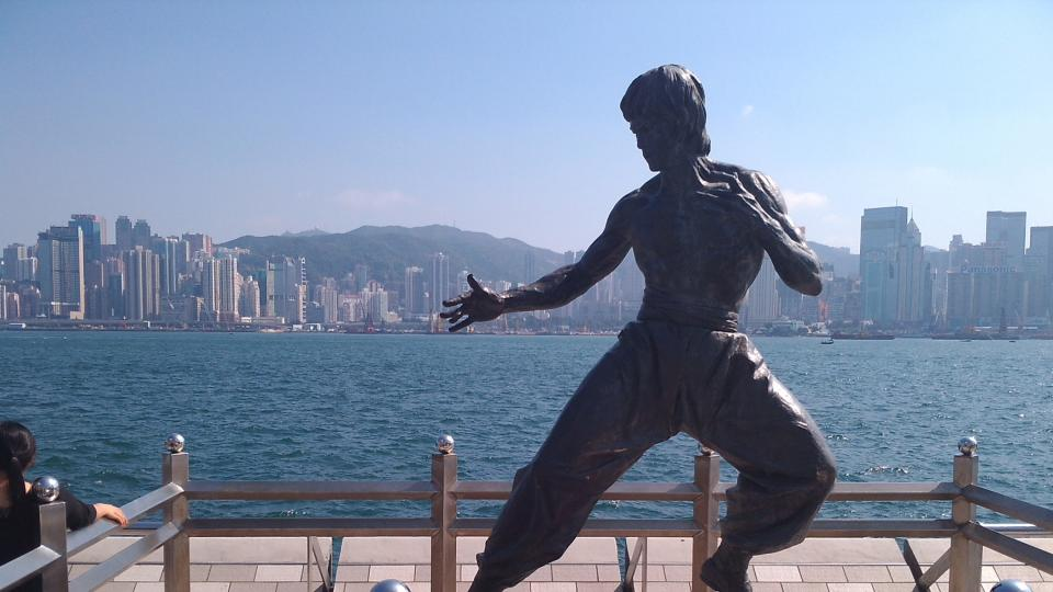 Jedna z raritních fotek bez davů turistů před ikonickou sochou Bruce Leeho na promenádě s výhledem na panorama severní části ostrova Hongkong